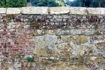 Old brick wall with sandstone and capping