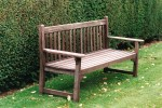 Traditional wooden bench with yew hedge