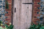 Wooden door in brick and flint wall